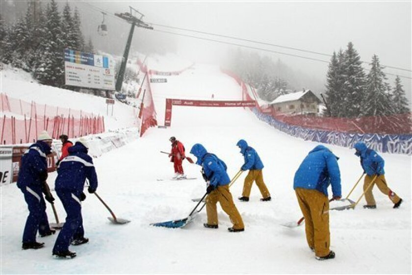Course workers clear the snow in the finish area ahead of a men's Alpine Ski World Cup downhill race ,in Val Gardena, Italy, Saturday, Dec. 15, 2012. (AP Photo/Armando Trovati)