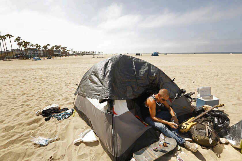 A homeless man sits near his belongings on a sandy beach.