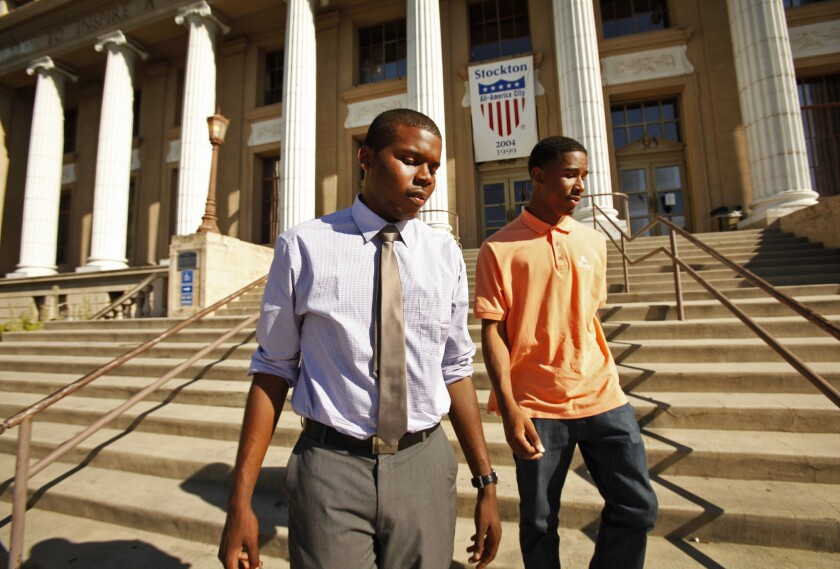 "Michael Tubbs, left, a recent Stanford graduate who won a City Council seat in Stockton, walks with a friend on the steps of City Hall last summer. After residents passed a tax measure Tuesday night to bring badly needed revenue for the bankrupt city, he said ""We're all breathing a little easier."""