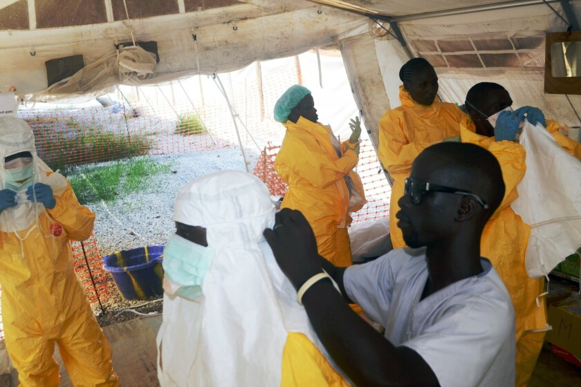 Members of Doctors Without Borders put on protective gear at a hospital isolation ward in Guinea.