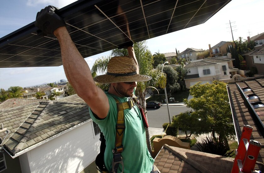 David Miller of SolarCity carries a photovoltaic panel ready to be installed on a home in Torrey Hills.