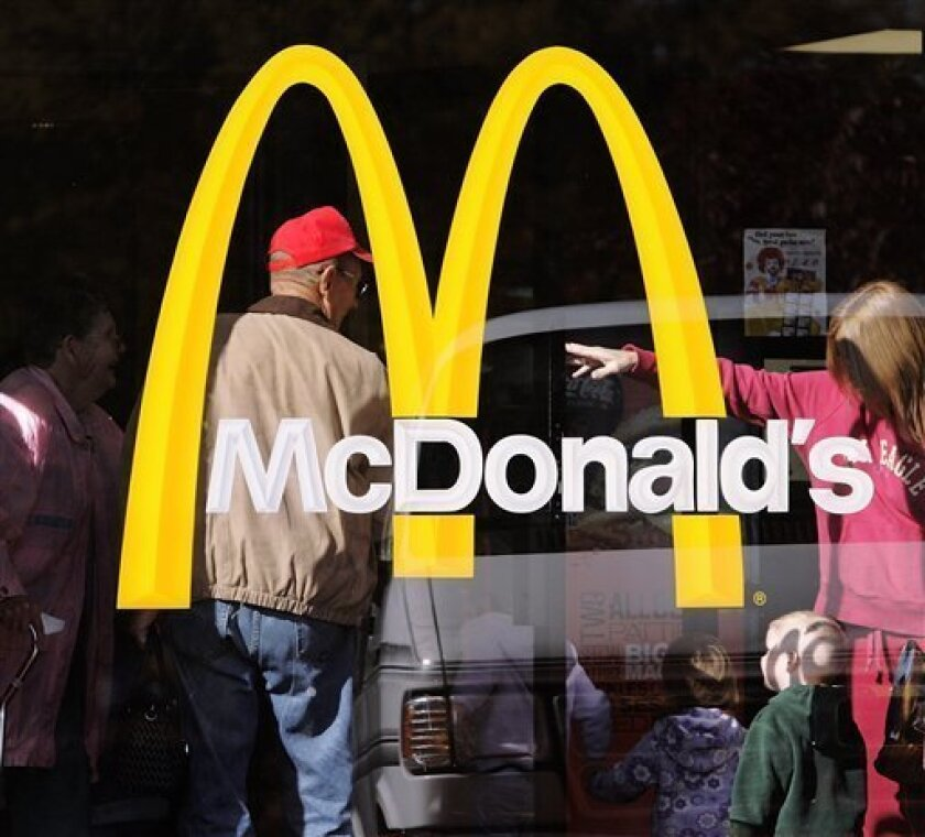 In this Oct. 21, 2008 file photo, a family looks for seating inside a McDonald's restaurant in Springfield, Ill. McDonald's said Monday, Dec. 8, 2008, sales at established locations jumped 7.7 percent worldwide in November with even recession-wary consumers in the U.S. buying more of the chain's burgers, fries and breakfast biscuits. (AP Photo/Seth Perlman, File)