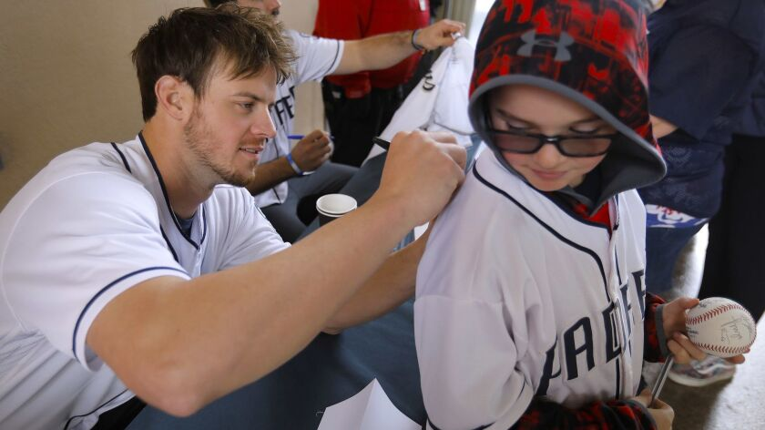 SAN DIEGO, CA 1/12/2019: Padres outfielder Wil Myers, left, signs an autograph on the back of Ethan