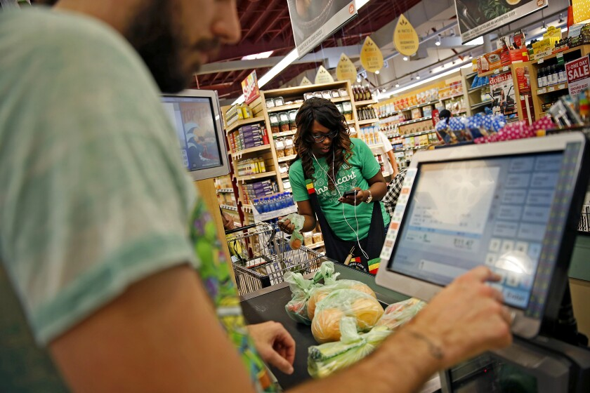 Whole Foods cashier Jason Ellsworth rings up groceries in 2014 as Instacart shopper Kara Pete uses a photo to double-check items ordered by a customer.