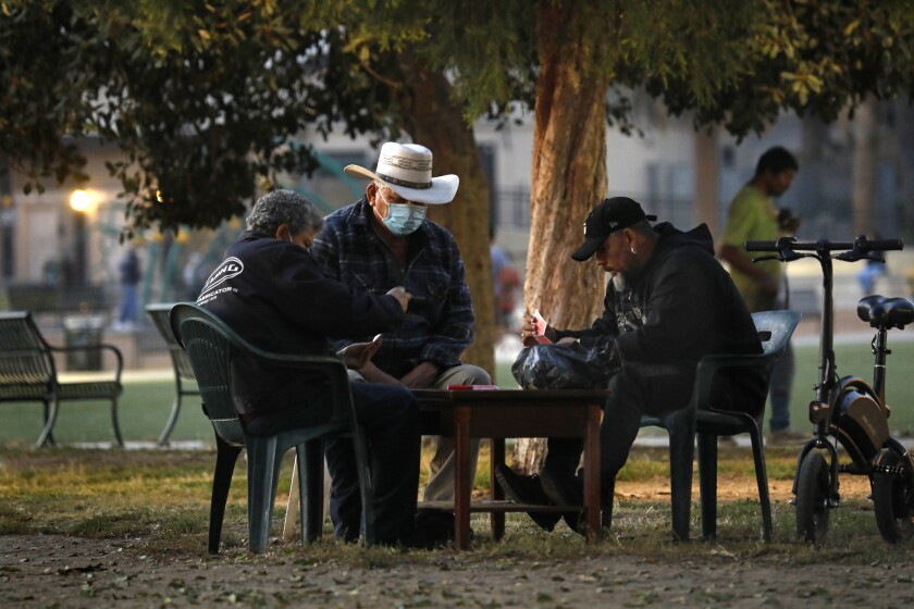 People play cards at MacArthur Park in Los Angeles on Thursday.