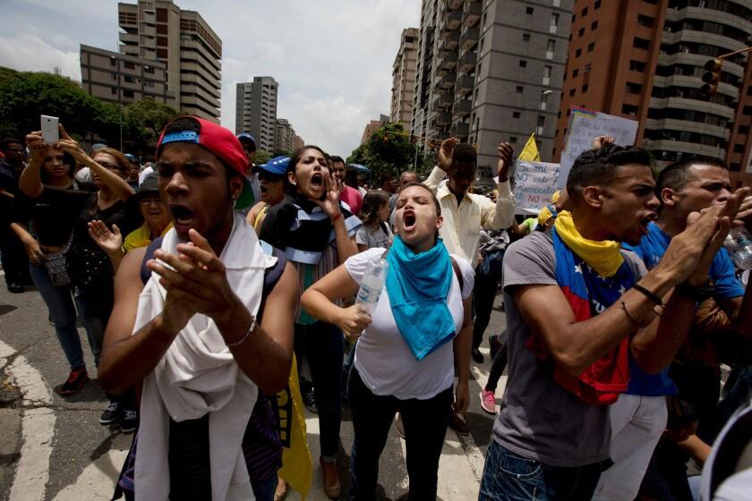 """Manifestantes contra el gobierno gritan """"Referendo"""" frente a una formación de la Policía Nacional Bolivariana que les impide marchar hacia el Consejo Nacional Electoral en Caracas, el miércoles 18 de mayo de 2016. (Foto AP/Fernando Llano)"""