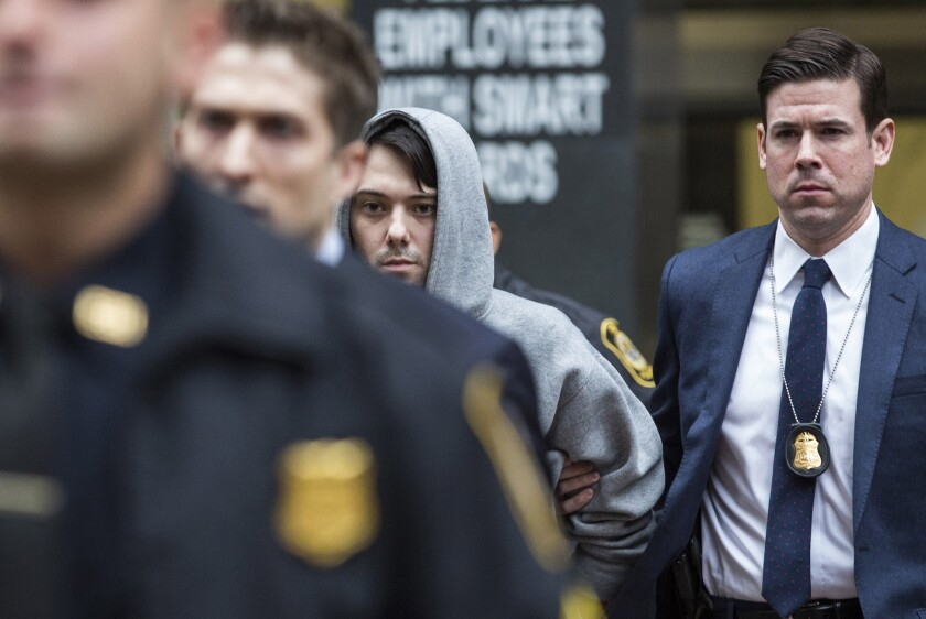 Not so brash anymore: Pharmaceutical pariah Martin Shkreli (in gray hoodie), escorted by federal agents after his arrest for fraud Thursday.