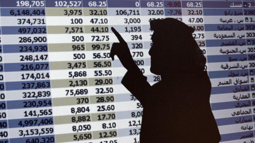 "The shadow of a Saudi trader is seen on a stock market monitor in Riyadh, Saudi Arabia, on Oct. 7, 2008. The Saudi stock market fell sharply Sunday after President Trump threatened ""severe punishment"" over the disappearance of Washington Post contributor Jamal Khashoggi."