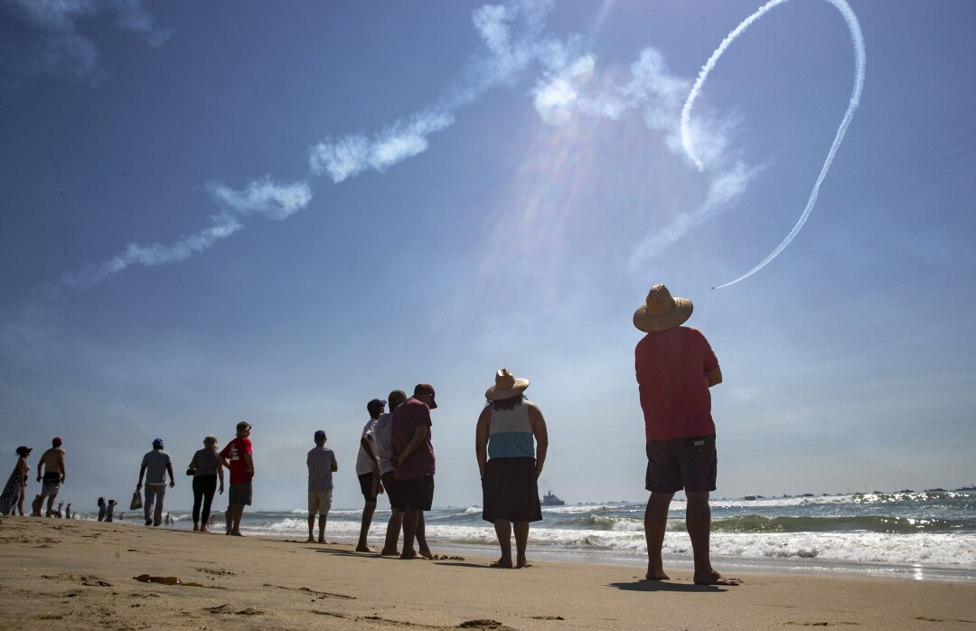 Spectators on the beach watch as a stunt plane pilot performs