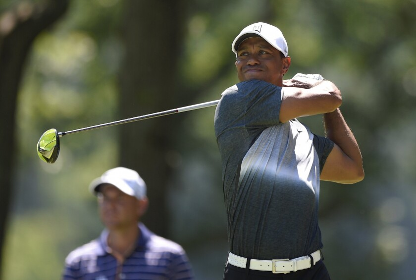 Tiger Woods watches his shot on the fifth tee during the second round of the Quicken Loans National golf tournament on Friday at the Robert Trent Jones Golf Club in Gainesville, Va.