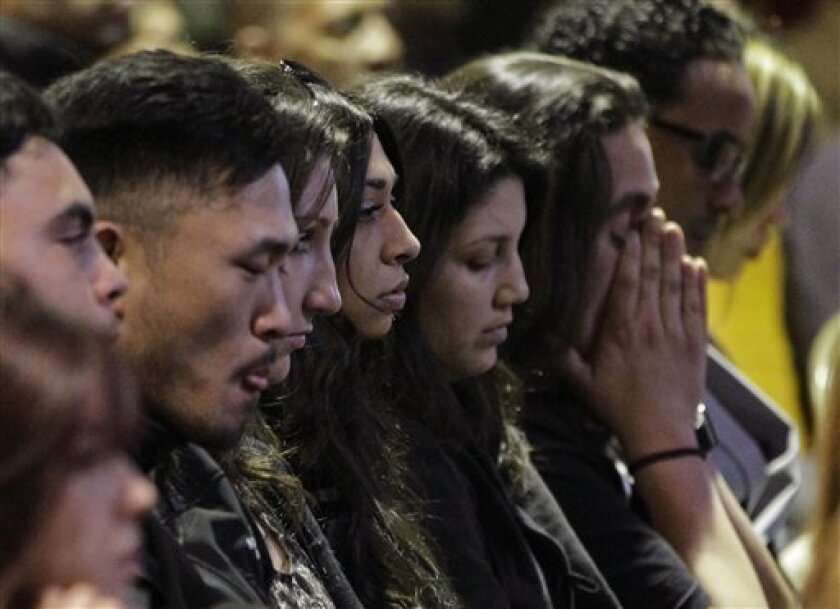 Mourners attend a memorial service at the Allen Temple Baptist Church Tuesday, April 3, 2012, in Oakland, Calif. Several hundred people gathered Tuesday night for a prayer vigil for the victims of Monday's shooting at Oikos University, a small Christian school in Oakland. (AP Photo/Ben Margot)