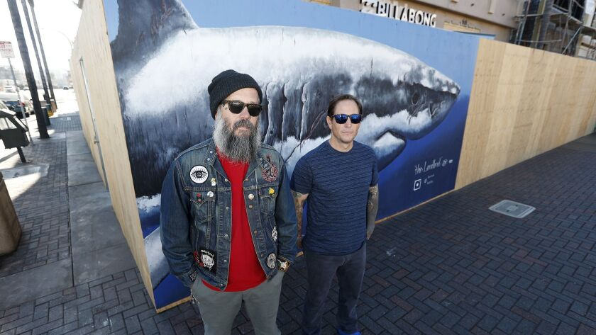 """Local artists Hector """"HEK"""" Valdez, left, and Dan McNab stand in front of """"the Landlord,"""" a 16-feet l"""