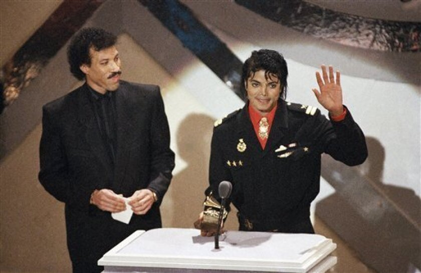 """FILE - In a Tuesday, Feb. 25, 1986 file photo, Michael Jackson and Lionel Richie receive a Grammy for best song of the year for their song """"We Are the World"""" at the 28th annual Grammy Awards in Los Angeles. Richie, a longtime friend to Michael Jackson, says the country is in need of some healing after the pop star's recent death and the Essence Music Festival in New Orleans is going to provide the perfect remedy. Essence, which begins Friday, July 3, 2009 and runs through Sunday, will feature performances by Richie, Beyonce, John Legend, Ne-Yo, Anita Baker and a host of other artists. Organizers are now also planning a special tribute to Jackson. (AP Photo/Lennox McLendon, File)"""