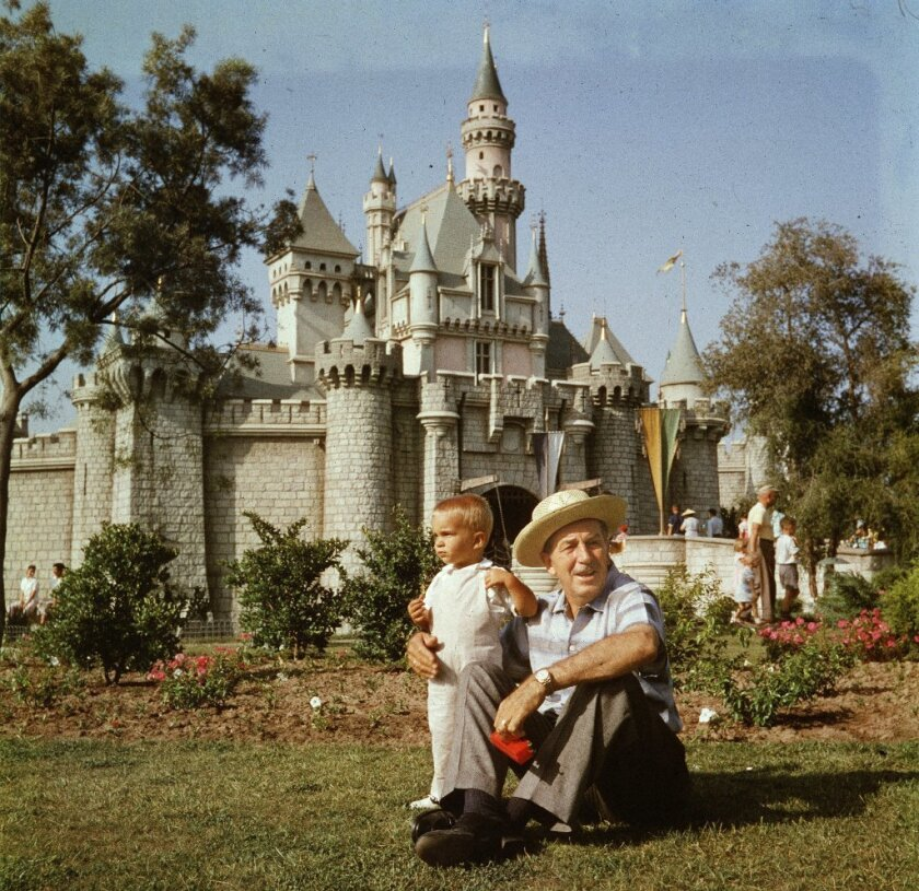 Walt Disney and his grandson Christopher Disney Miller relax near Sleeping Beauty Castle in the 1950s.