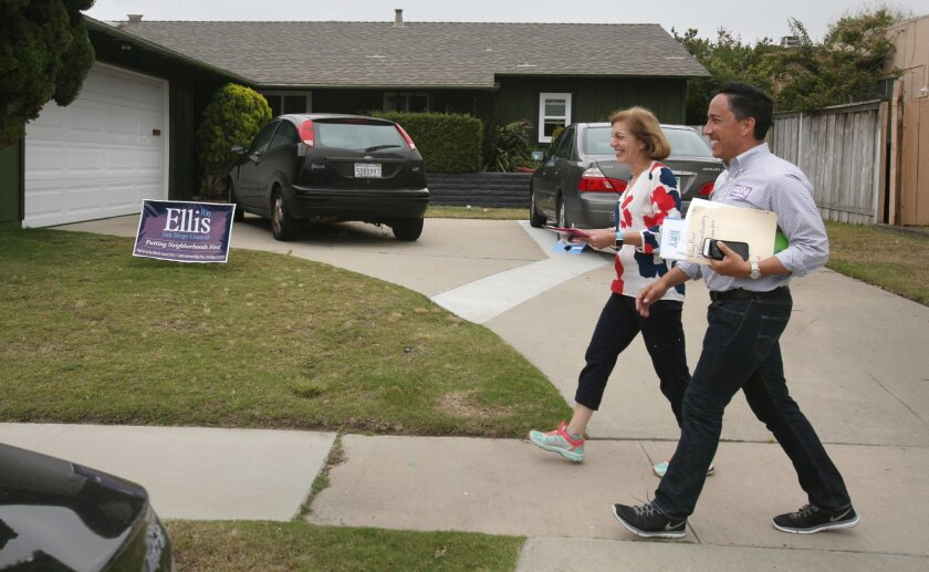 San Diego City Councilman Todd Gloria, a candidate for the state assembly, and Barbara Bry, candidate for the city council, walk past a sign for her competitor, Tuesday afternoon while knocking on doors last minute, reminding people to vote.