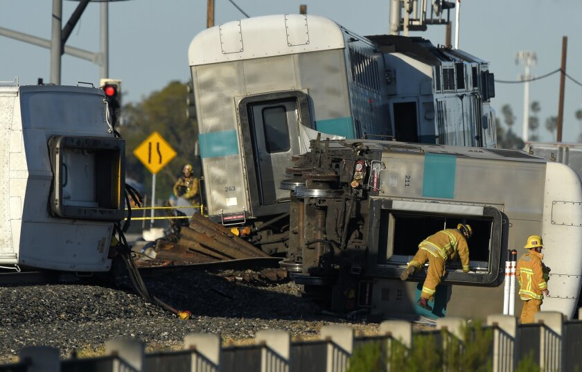 A firefighter climbs into the wreck of a Metrolink passenger train that derailed, Tuesday, Feb. 24, 2015, in Oxnard, Calif. Three cars of the Metrolink train tumbled onto their sides, injuring dozens of people in agricultural country 65 miles northwest of Los Angeles. Metrolink spokesman Scott John