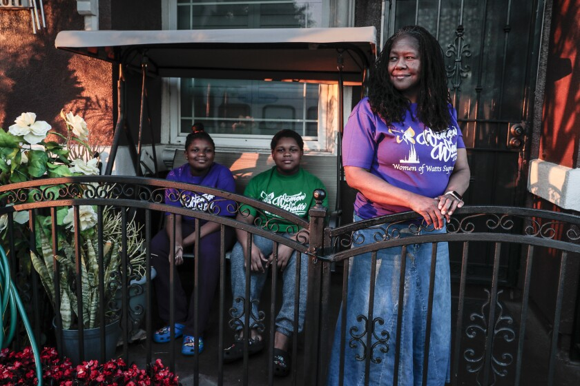 A grandmother stands with her two young grandsons outside their home.