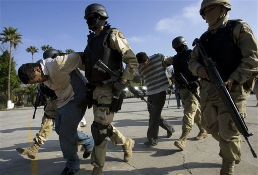 FILE - This Dec. 3, 2008 file photo shows Mexican Army soldiers holding two suspects, arrested during an operation against drug smuggling and kidnapping gangs, after being presented to the press in Tijuana, Mexico. (AP Photo/Guillermo Arias, File)