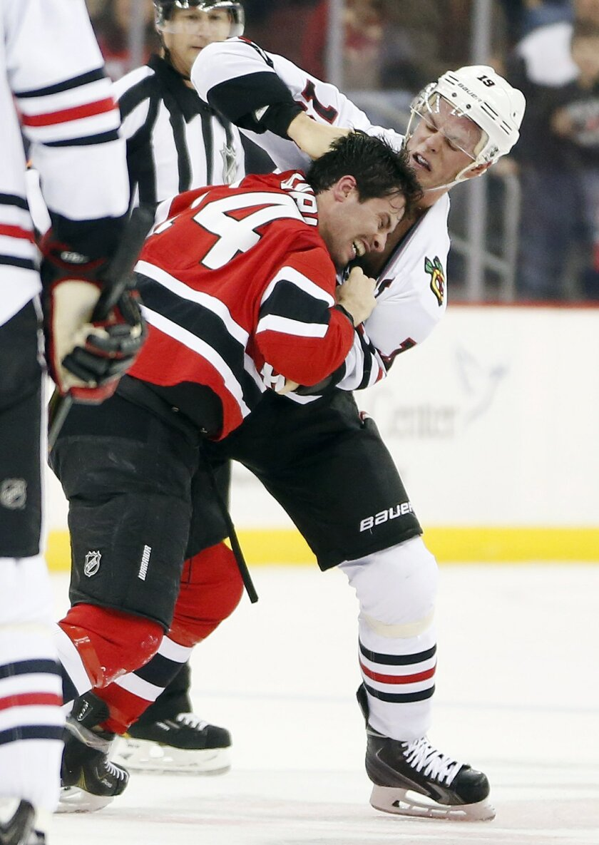 Chicago Blackhawks center Jonathan Toews, right, fights with New Jersey Devils center Adam Henrique during the first period of an NHL hockey game Friday, Nov. 6, 2015, in Newark, N.J. (AP Photo/Julio Cortez)