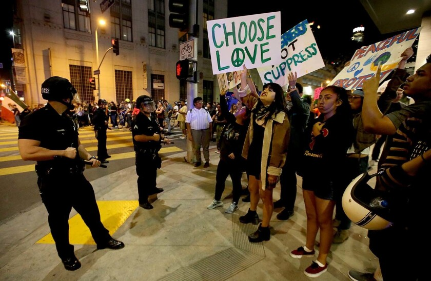 Protesters chant and wave signs as LAPD officers halt their march through downtown Los Angeles.
