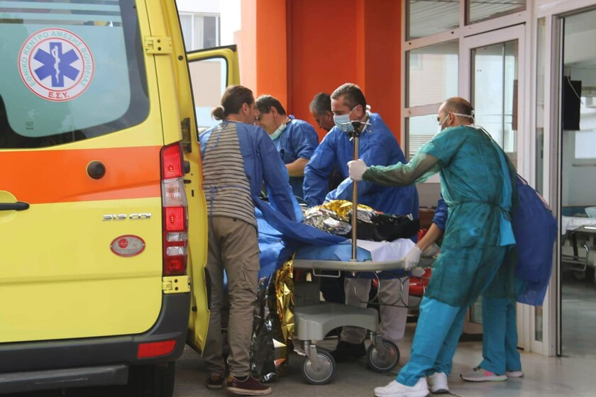 A survivor from a boat full of migrants that sank off the Greek coast is wheeled into an emergency room in the port town of Preveza on Saturday.