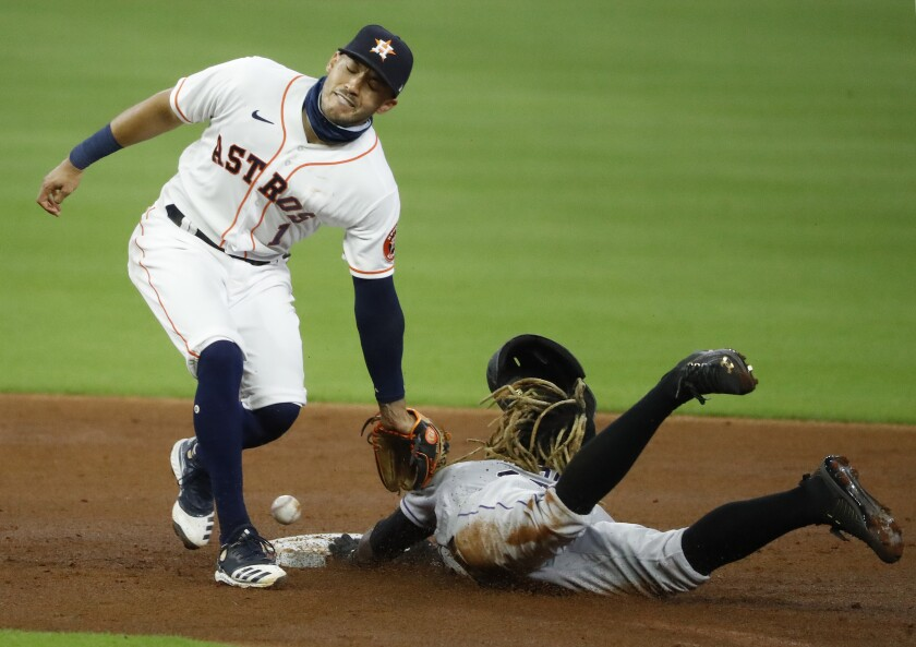 Houston Astros shortstop Carlos Correa can't contain a throwing error from catcher Dustin Garneau as the Colorado Rockies' Raimel Tapia steals second base in the top of the second inning on Monday, Aug. 17, 2020, in Houston. (Kevin M. Cox/The Galveston County Daily News via AP)