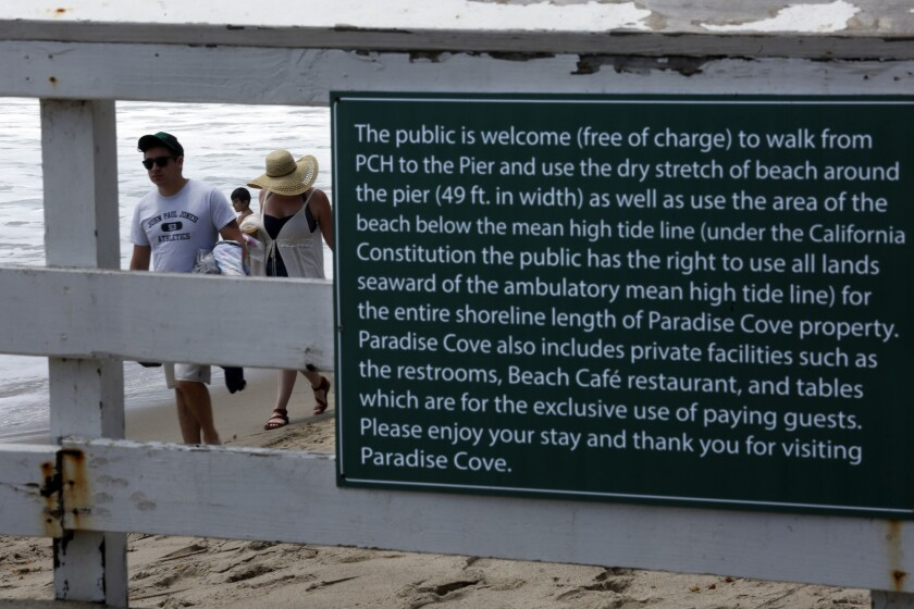 A sign is posted on the Paradise Cove Pier that instructs visitors on what areas of their property is open to the public at Paradise Cove.