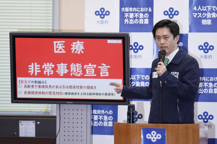 """Osaka Gov. Hirofumi Yoshimura speaks next to a screen reading """"medical emergency declaration"""" in Osaka, western Japan, Wednesday, April 7, 2021. Osaka prefecture issued a special warning Wednesday over the rapid upsurge of the coronavirus cases that has put the area's medical systems on the brink of collapse, requesting the cancellation of the Olympic torch relay on public roads. (Nobuki Ito/Kyodo News via AP)"""