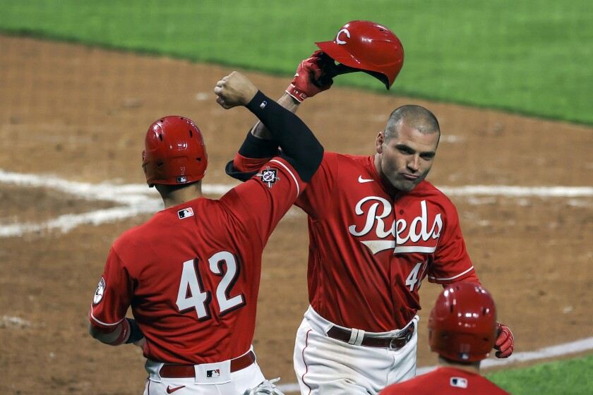 Cincinnati Reds' Eugenio Suarez, left, celebrates the two-run home run by Joey Votto, right, during the third inning of a baseball game against the Cleveland Indians in Cincinnati, Friday, April 16, 2021. (AP Photo/Aaron Doster)