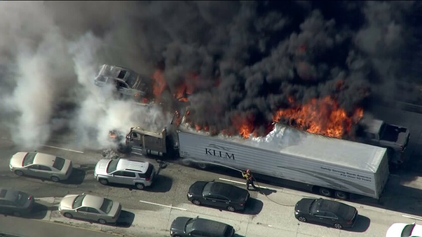 A big-rig burns on the 15 Freeway in the Cajon Pass as a brush fire that has grown to more than 3,500 acres moves toward two mountain communities.