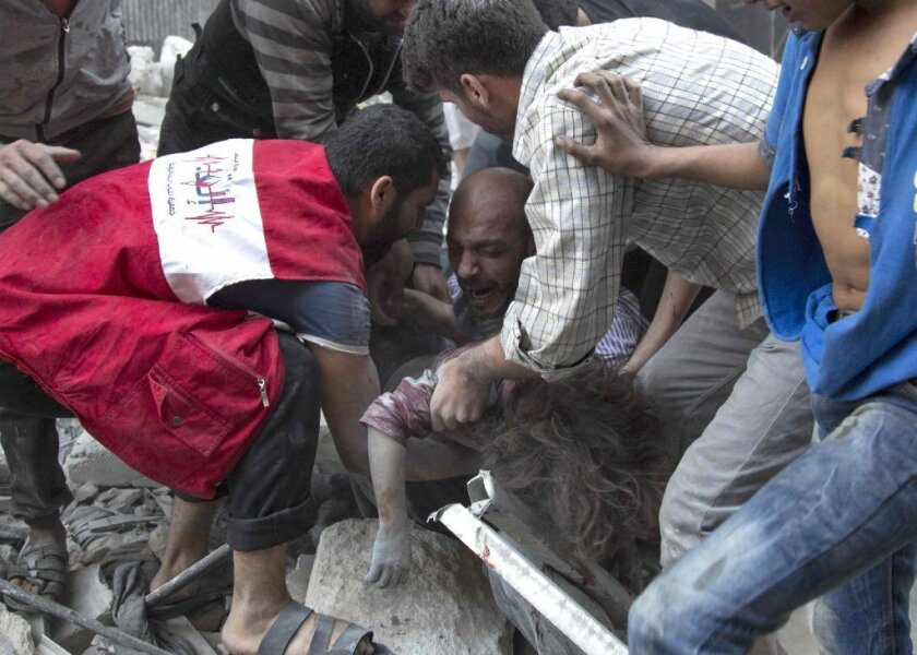 A man cries over the body of his child after she was pulled from the rubble of a bombed building in a rebel-held neighborhood in Aleppo, Syria, this week.