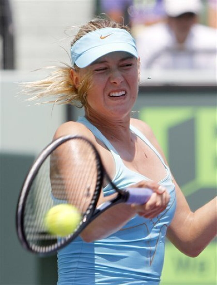 Maria Sharapova, of Russia, returns to  Andrea Petkovic during a semifinal match at the Sony Ericsson Open tennis tournament in Key Biscayne, Fla., Thursday, March 31, 2011. Sharapova won 3-6, 6-0, 6-2. (AP Photo/Alan Diaz)