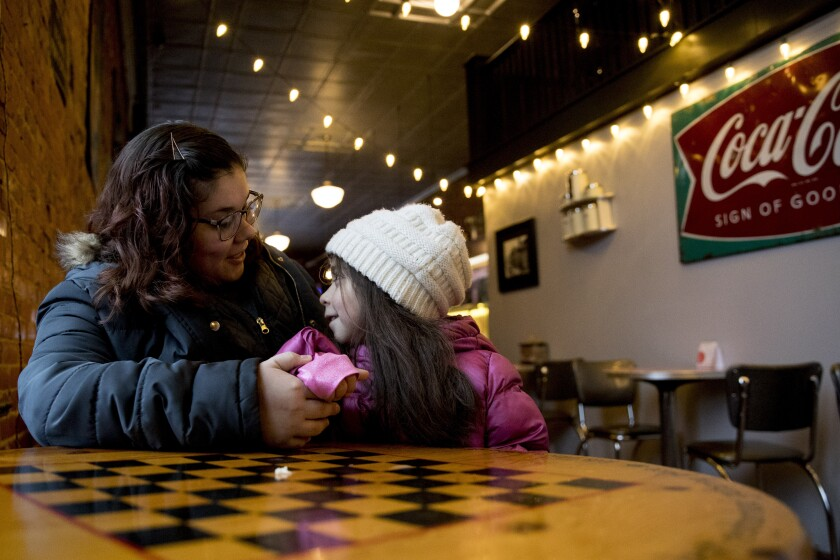 In this Jan. 24, 2020, photo, Mary Oldham, 27, a middle school science teacher from Knoxville, Iowa poses for a photograph with her daughter Kailyn, 6, at Smokey Row Coffee, in Pella, Iowa. Oldham was never much into politics but says her boyfriend has gotten her thinking: If you don't vote, you don't have a voice. So Oldham is planning to caucus Monday, Feb. 3 — for a Democrat. (AP Photo/Andrew Harnik)