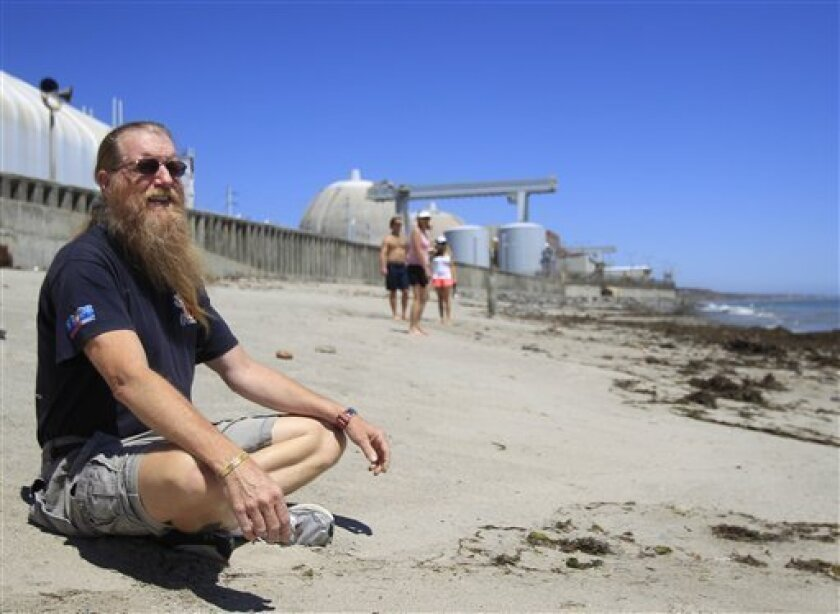 "In this Thursday, June 30, 2011 picture, Bret Gross, a resident of San Clemente, Calif., sits on the beach just outside the San Onofre Nuclear Generating Station, about five miles from his home. He worries that the area cannot be quickly evacuated in a severe nuclear accident. ""Forget the amount of training and plans,"" he said. ""It'll be ugly."" (AP Photo/Lenny Ignelzi)"