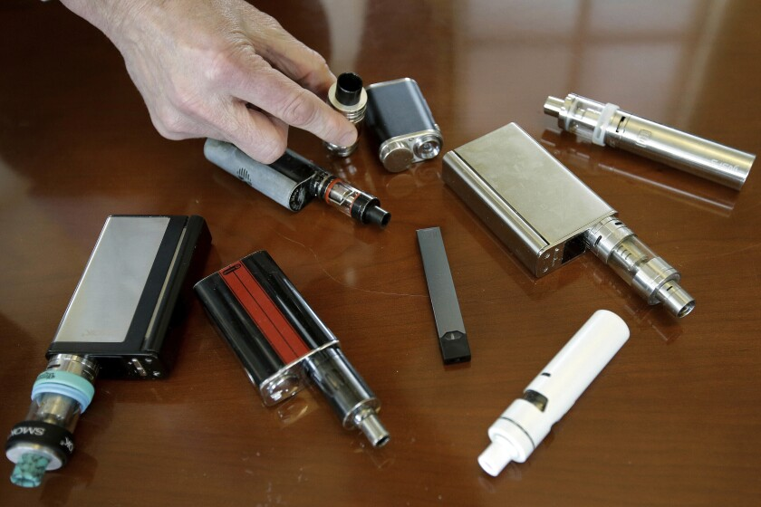 FILE - In this Tuesday, April 10, 2018 photo, a high school principal displays vaping devices that were confiscated from students at the school in Massachusetts. On Thursday, Sept. 26, 2019, the Centers for Disease Control and Prevention said 805 confirmed and probable cases have been reported to have a vaping-related breathing illness, and the death toll has risen to 12. (AP Photo/Steven Senne)