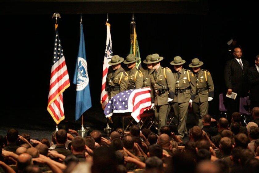 Uniformed agents carry the flag-draped casket of Border Patrol Agent Robert Rosas into the memorial service Friday morning. (JOHN GIBBINS / Union-Tribune)