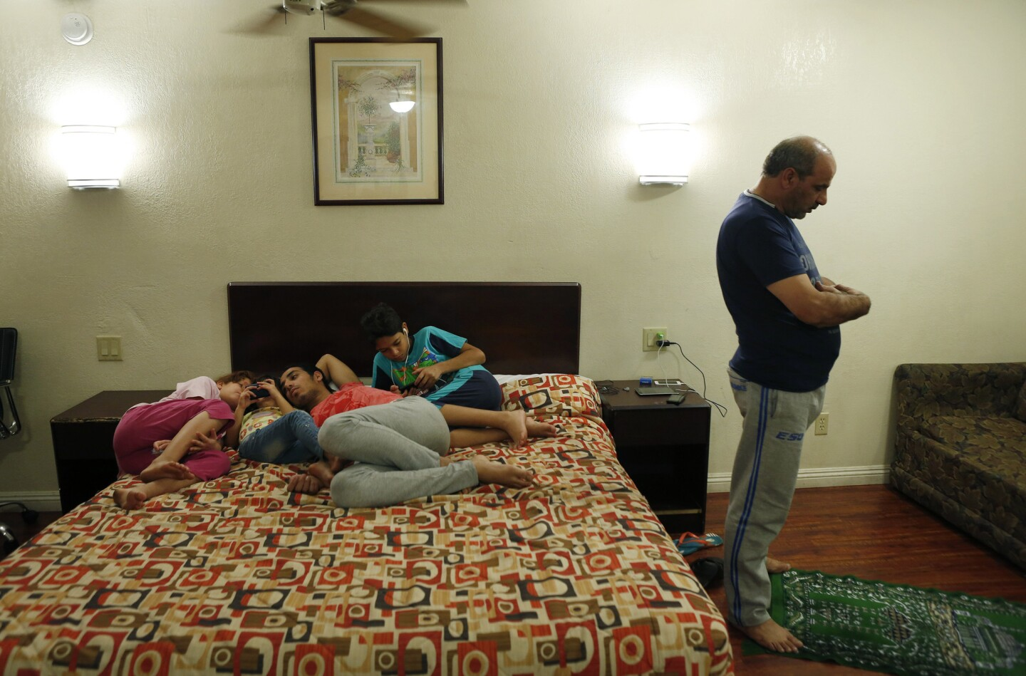 Fouad Wawieh, right, prays in his family's motel room in Pomona as four of his six children -- Maram, 9, left; Massa, 5; Omar, 19; and Omran, 12 -- use the family's smartphones. The family escaped from Syria via Egypt to arrive in the U.S.