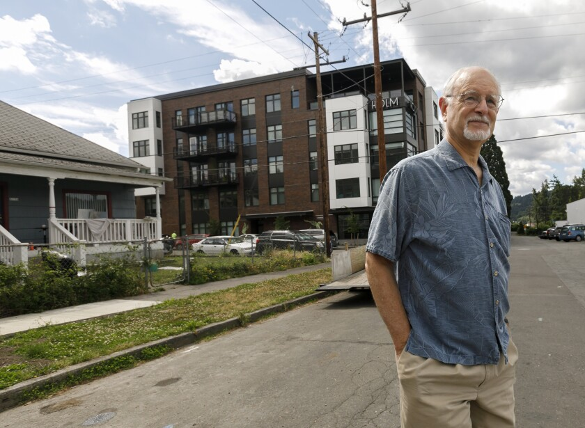 Rod Merrick, president of the Eastmoreland Neighborhood Assn., looks at a large complex in a southeast Portland, Ore., neighborhood, constructed next to a single family home in July.