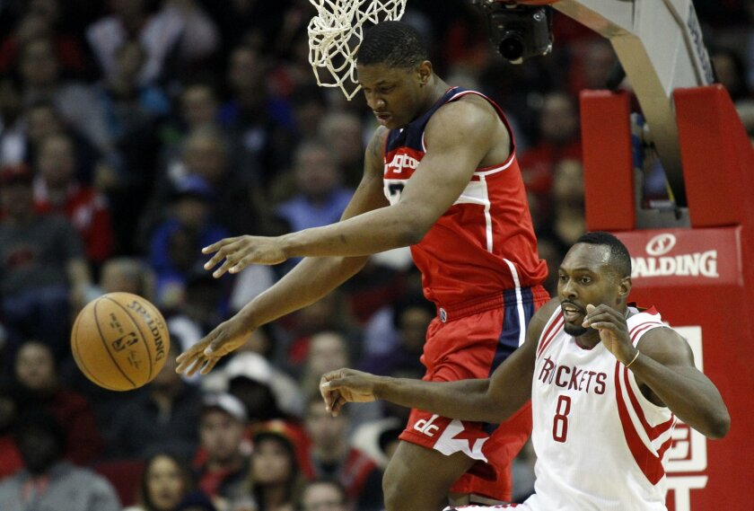 Houston Rockets center Dwight Howard (8) and Washington Wizards Bradley Beal go after a rebound during the second quarter of an NBA basketball game, Monday, Dec. 29, 2014, in Houston. (AP Photo/Patric Schneider)