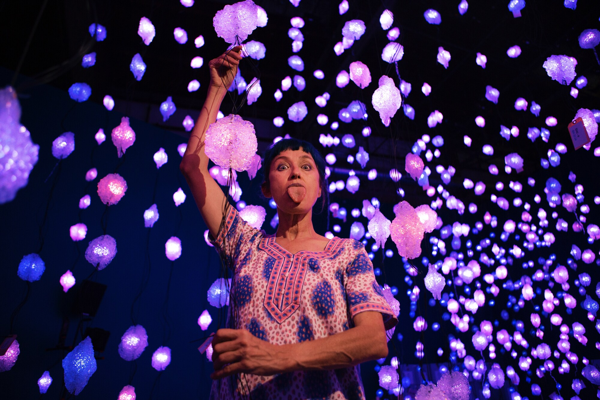 Pipilotti Rist sticks out her tongue while standing amid dozens of pink and purple lights that dangle from the ceiling.