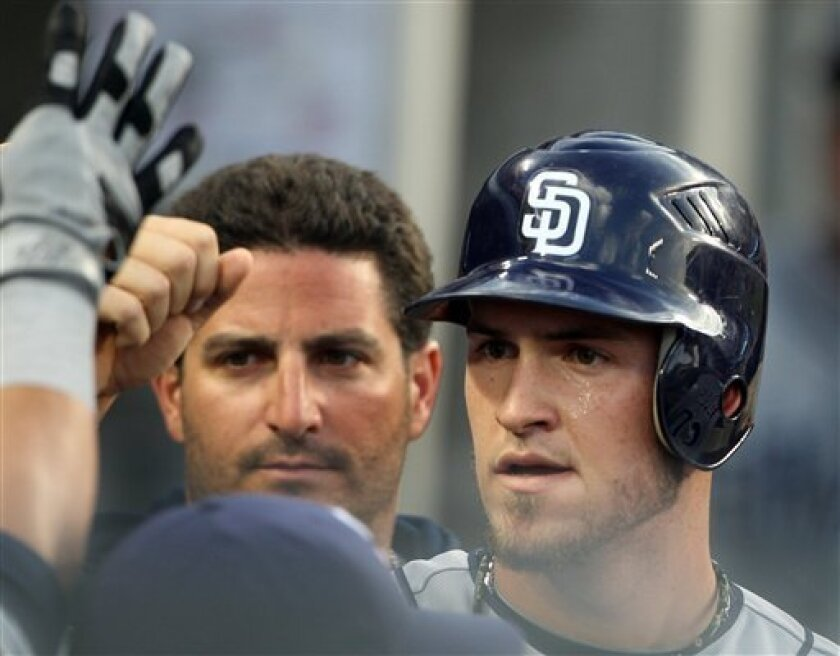 The San Diego Padres' Yasmani Grandal, right, celebrates with teammates after scoring on an Everth Cabrera ground out against the Los Angeles Dodgers in the second inning of a baseball game in Los Angeles, Friday, July 13, 2012. (AP Photo/Reed Saxon)