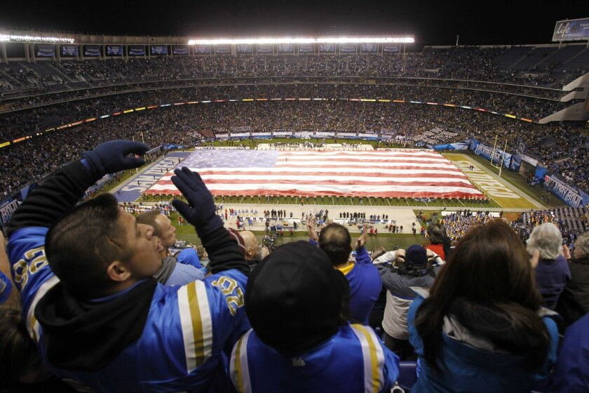 With a large American flag covering the field, UCLA fans cheer as the National Anthem is played during the Holiday Bowl at Qualcomm Stadium in San Diego on Thursday.