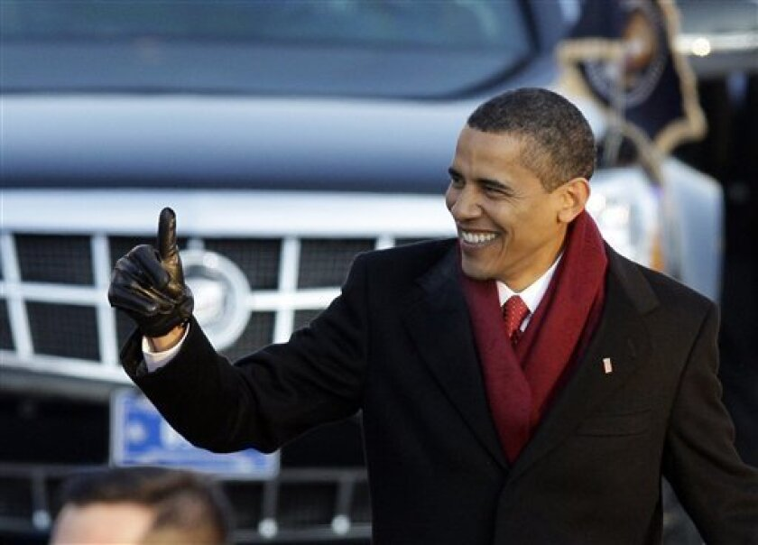 President Barack Obama gives a thumbs up as he walks down Pennsylvania Avenue on his way to the White House in Washington Tuesday, Jan. 20, 2009.(AP Photo/Alex Brandon)