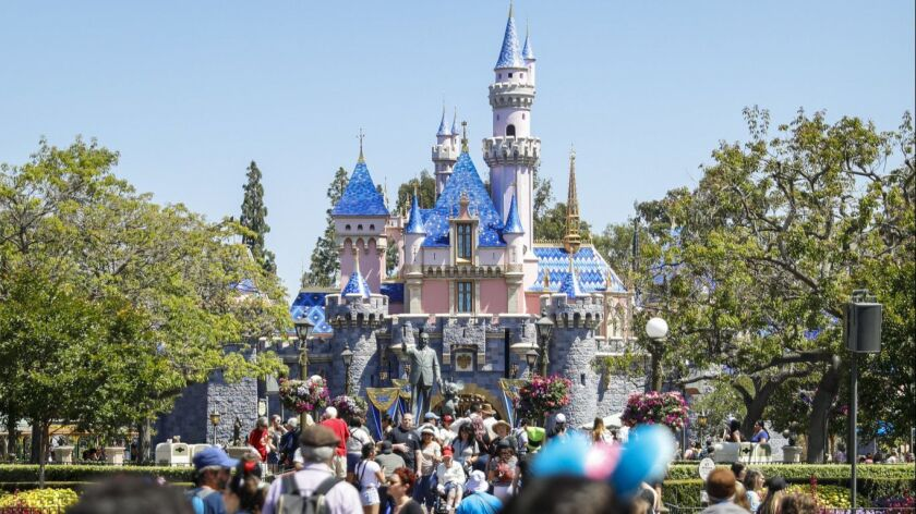The Sleeping Beauty Castle rises above crowds at Disneyland in Anaheim in May.
