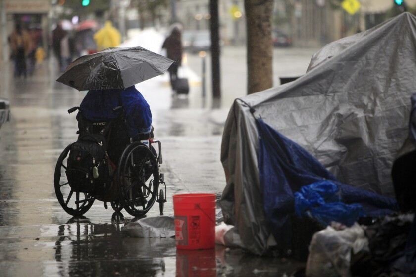 A 26-year-old woman who lives on skid row attempts to stay dry during a rainstorm on Dec. 2, 2014.