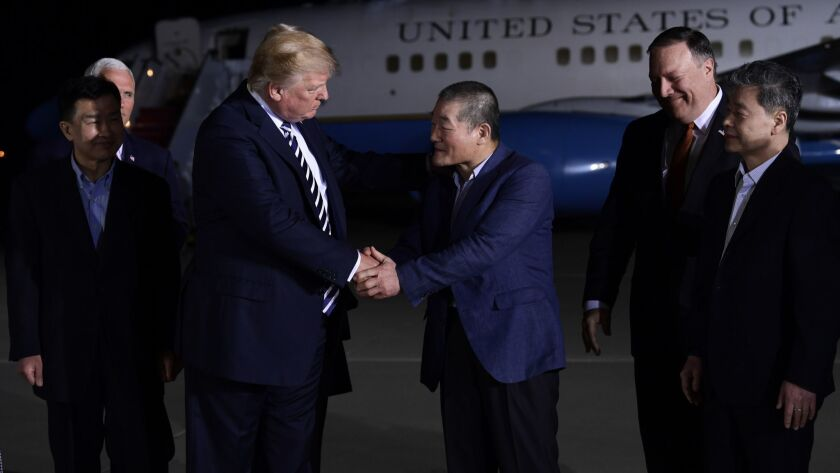 President Donald Trump, center left, shakes hands with Kim Dong Chul, with Tony Kim, far left and Ki