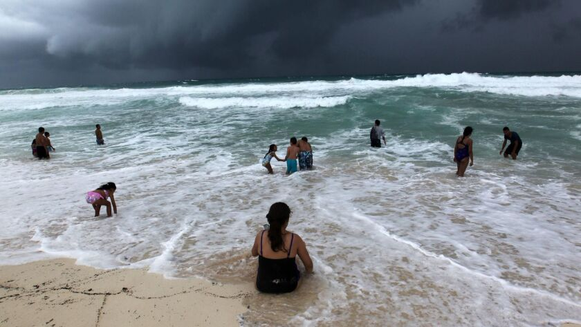 People swim in the turbulent sea in Cancun, Mexico, on Sunday, as a tropical depression that was moving toward Florida was upgraded to a named tropical storm, Michael.
