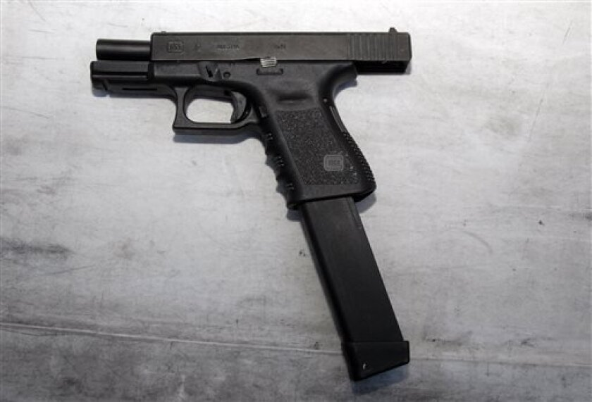 A Glock 9mm gun with an extended magazine used in the Tucson shooting rampage that killed six people and wounded former U.S. Rep. Gabrielle Giffords and 12 others in January 2011.