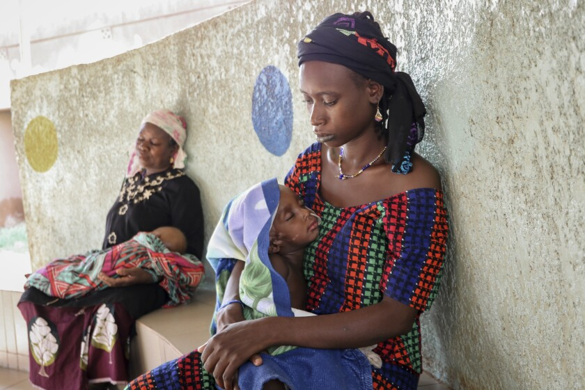 Fatima Li holds her 2-year-old son as he is treated with a feeding tube in Burkina Faso on June 22.