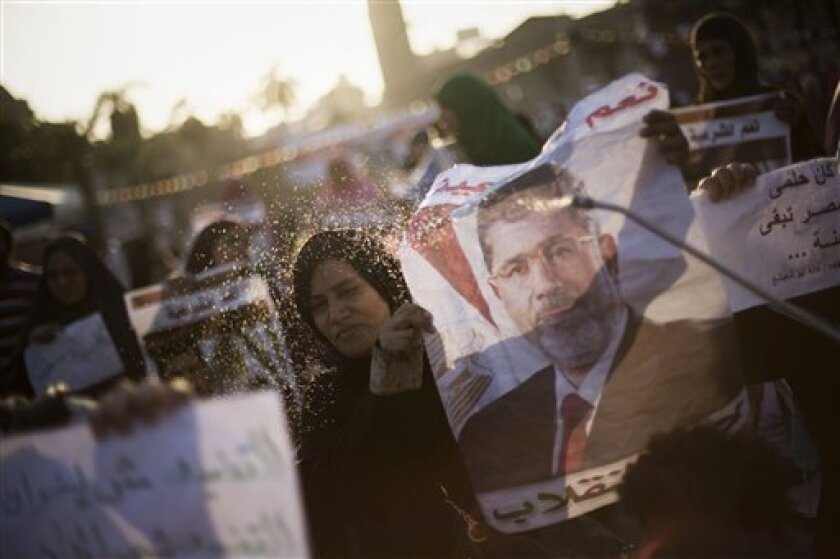 """A supporter of Egypt's ousted President Mohammed Morsi sprays water on an Egyptian woman during a protest near Cairo University in Giza, Egypt, Thursday, August, 1, 2013. Authorities offered """"safe passage and protection"""" Thursday for thousands of supporters of ousted President Mohammed Morsi if they end their two large sit-ins in Cairo. The Interior Ministry's offer appears to be the first step by Egypt's new leadership to clear away the Morsi supporters from where they have been camped since sh"""
